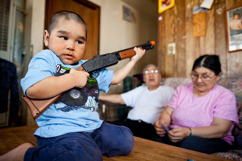 3 year old Shane Miles Akeya plays with his toy gun at home in Savoonga